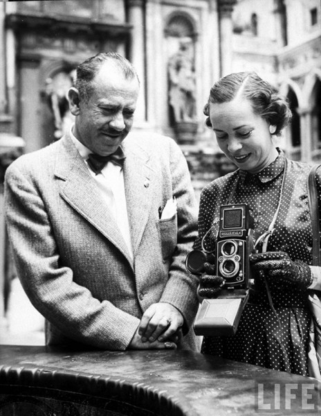 American novelist John Steinbeck standing beside wife, writer Elaine Andersen, who is using Rolleiflex camera around neck